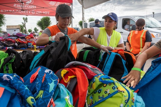 Volunteers sift through backpacks during the Victor Valley Rescue Mission's annual backpack giveaway at the San Bernardino County Fairgrounds in Victorville on Thursday, July 29 2021.