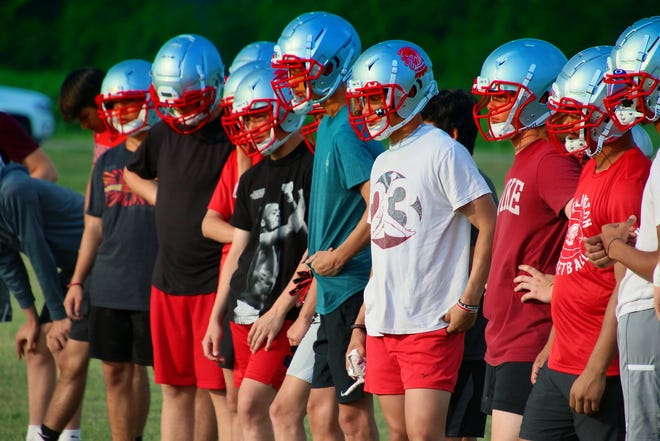 Wellington football players listening to coach before practice