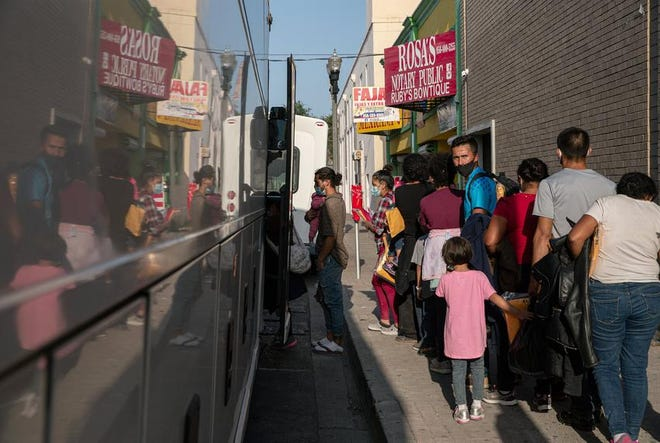 A group of migrants wait to board a charter bus in front of the Catholic Charities RGV Humanitarian Respite Center in McAllen on Tuesday.