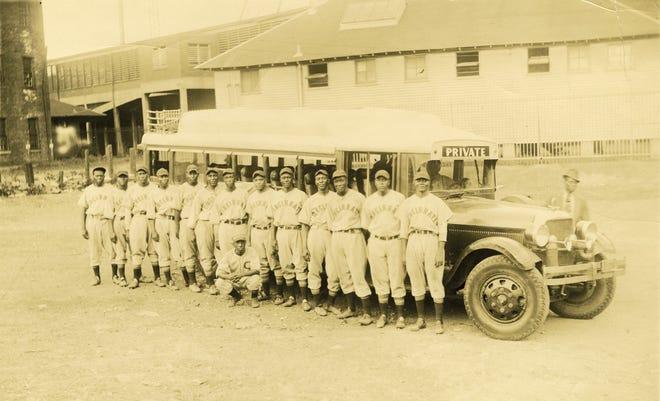 The Negro Leagues team of the Cincinnati Tigers in 1936 standing beside their team bus outside of Crosley Field.