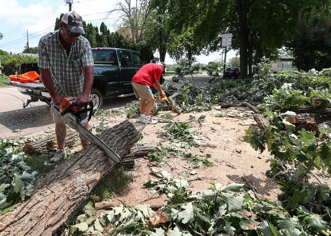 Steve Renderman (left) helps a Ripon home owner cut up a fallen tree Thursday, July 29, 2021 on Shepard Street in Ripon, Wis. A line of severe storms raked through the area overnight causing widespread tree damage. Doug Raflik/USA TODAY NETWORK-Wisconsin