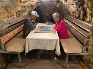 Hak (left) and Ung Shin spend time in a tunnel at the Merry Widow Health Mine in Basin, Montana, on June 30 piecing together a puzzle. For more than a decade, the California couple have made the trip to expose themselves to radioactive radon, which they say keeps them healthy.