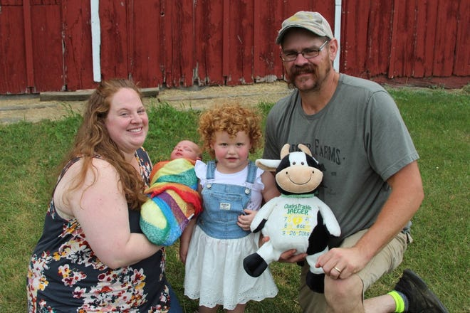 Megan and Jason Jaeger pose for a family picture with newest addition Josie, born July 14, Guinevere, 2, and a stuffed cow representing Charles, the child they lost in 2018.