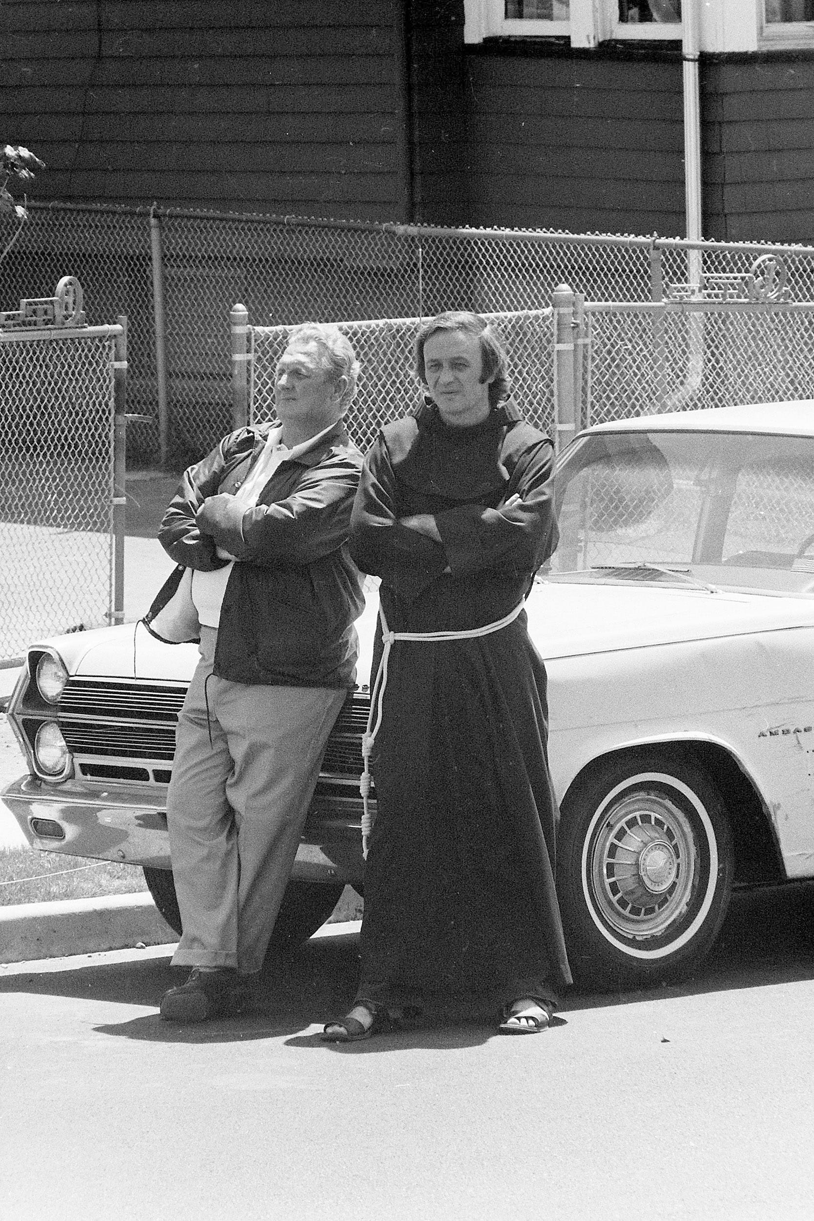 Judge Fred C. Galda and Father Mychal Judge wait between negotiations during a police standoff with James G. Hyams who was holding his wife and their three children hostage in his wife's home with a shotgun and two handguns in Carlstadt, N.J., on May 19, 1974. During the all-day seige, Hyams had fired three shots and police fired one. No one was injured.