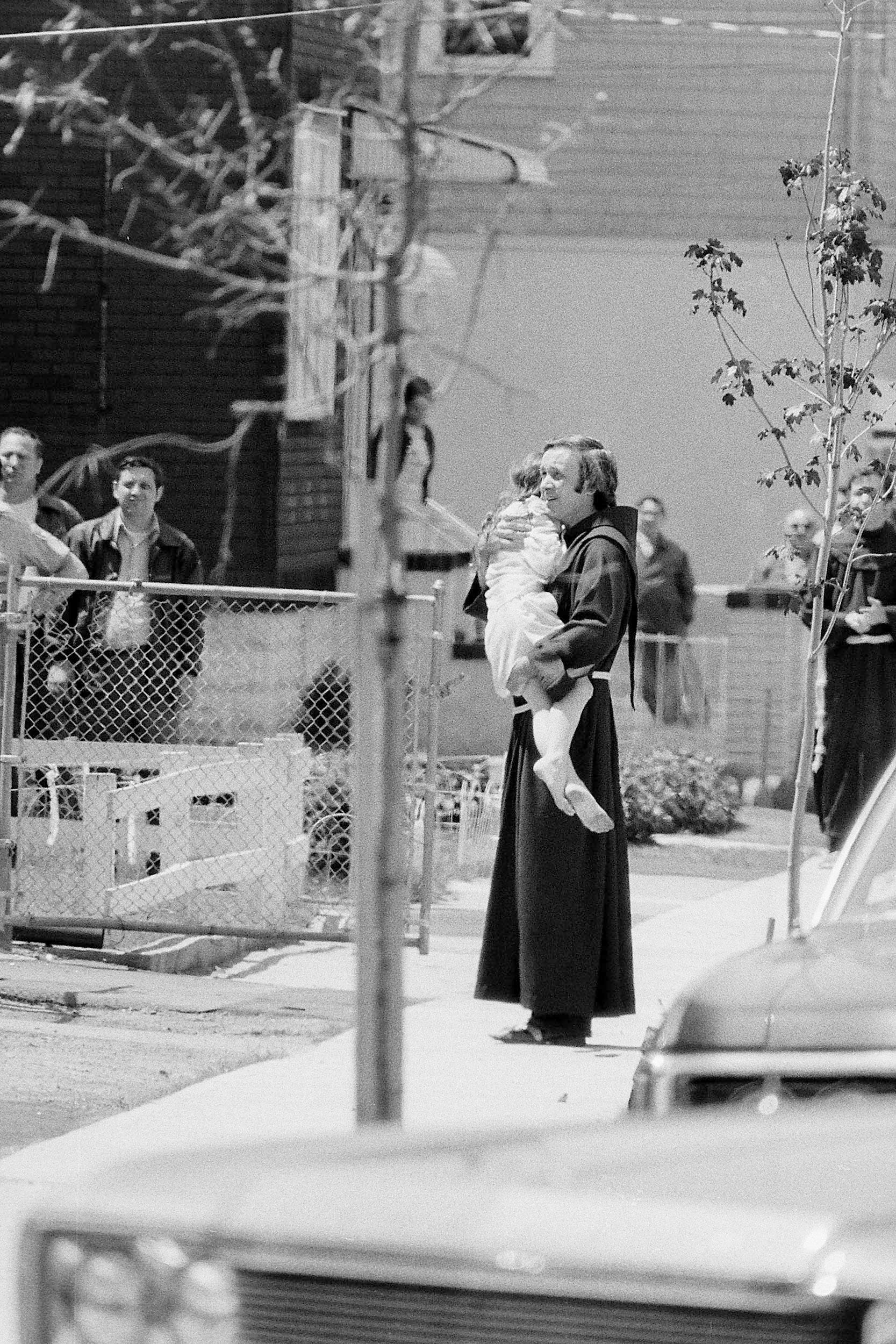 Father Mychal Judge comforts one of the Hyams children during a police standoff with James G. Hyams who was holding his wife and their three children hostage in his wife's home with a shotgun and two handguns in Carlstadt, N.J., on May 19, 1974. During the all-day seige, Hyams ahd fired three shots and police fired one. No one was injured.