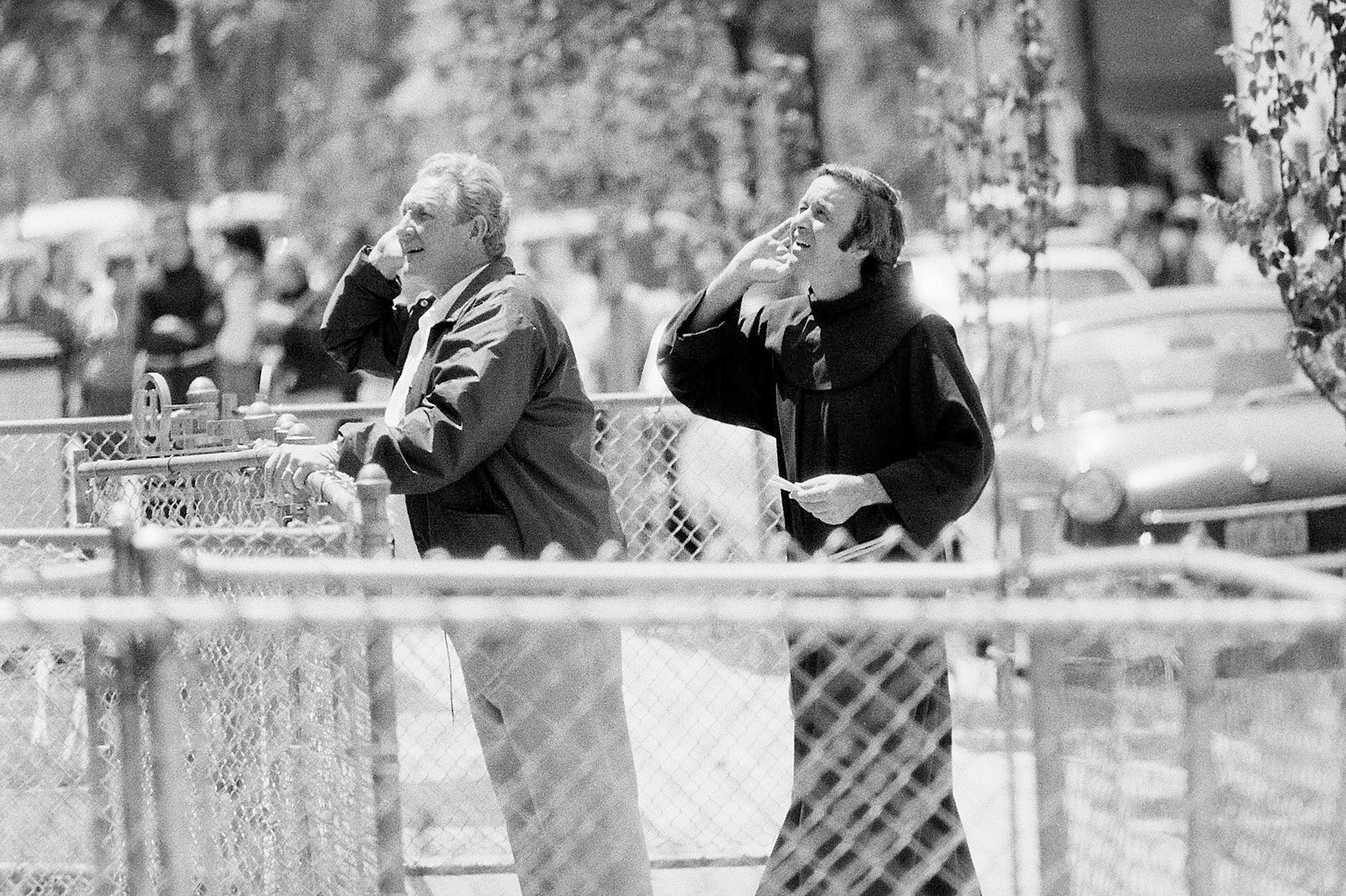 Judge Fred C. Galda and Father Mychal Judge listen to requests from inside the house during a police standoff with James G. Hyams who was holding his wife and their three children hostage in his wife's home with a shotgun and two handguns in Carlstadt, N.J., on May 19, 1974. During the all-day seige, Hyams had fired three shots and police fired one. No one was injured.