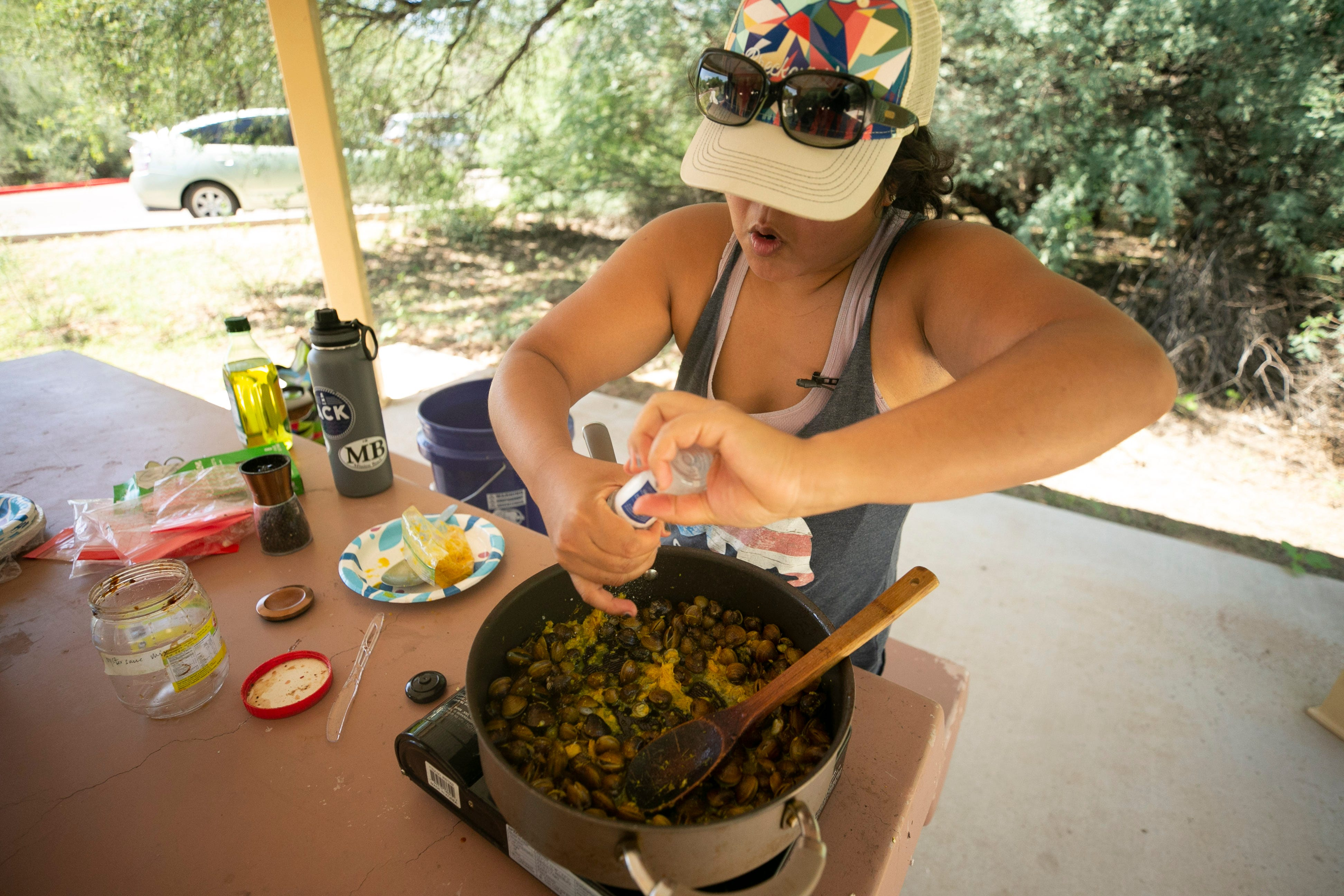 Jenneen Sambour of Phoenix stir-fries Asiatic clams just taken from the Verde River with Kroeung, a Cambodian marinade and spice paste at the Needle Rock Recreation Site outside of Rio Verde on July 28, 2021.