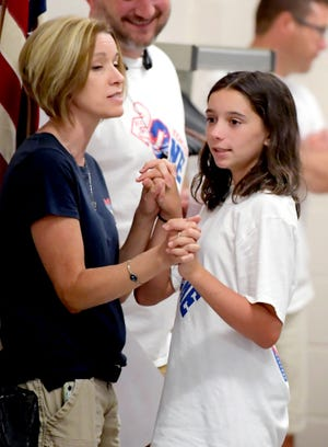 Spring Grove swimmer Addy Daily, 11, talks with her mother Kelly at a Hali Flickinger watch party at Spring Grove Middle School Wednesday, July 28, 2021. They joined a crowd gathered to watch Flickinger, a Spring Grove High School graduate, swim in the Olympic 200-meter butterfly final. Bill Kalina photo