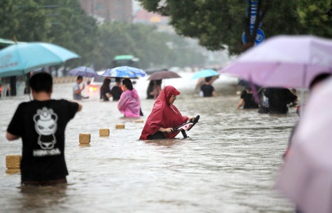 People walk in the flooded road after record downpours in Zhengzhou, in central China's Henan province, on July 20, 2021. (Featurechina/ROPI/Zuma Press/TNS) * France, Germany and Italy Rights Out *