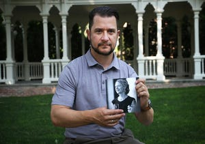 Yani Dickens poses for a portrait on the campus of the University of Nevada, Reno while holding a photograph of his late wife Jessica on July 29, 2021.