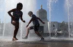 Children, with a summer program hosted by Farmworker Housing Development Corporation, play in the Wall of Water fountain on the Capitol Mall Thursday. Forecasts call for temperatures reaching near 100 degrees in Salem again on Friday.