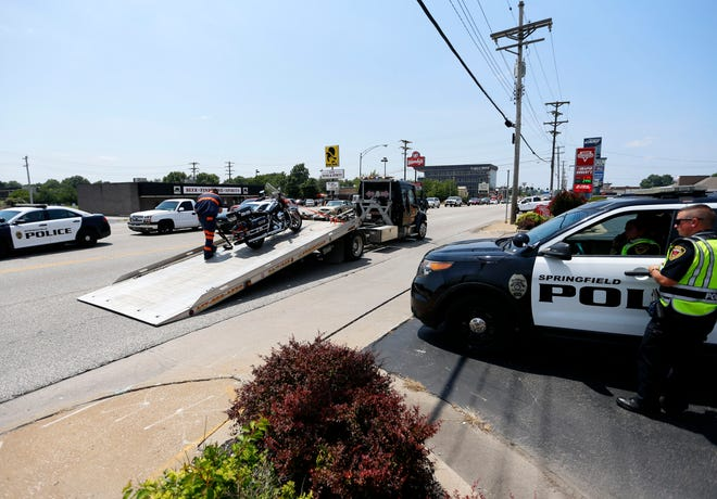 A Springfield Police motorcycle is loaded onto the back of a flatbed tow-truck after an accident on East Sunshine near U.S. 65 on Thursday, July 29, 2021. One officer was taken to a hospital after the accident.
