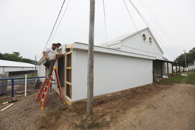 A crew from Hostetler Buildings puts the finishing touches on a new addition to the coliseum at the Muskingum County Fairgrounds on Thursday.