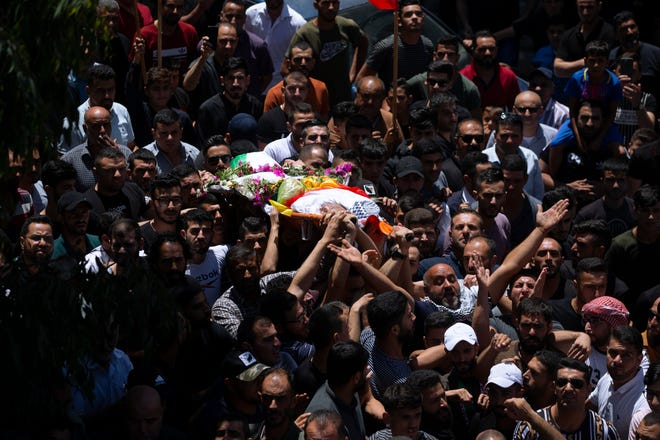 Palestinians carry the body of Mohammed al-Alami, 12, during his funeral July 29 in the village of Beit Ummar, near the West Bank city of Hebron. Villagers say the boy was fatally shot by Israeli troops while traveling with his father in a car. The Israeli military has launched an investigation into the shooting.