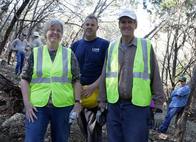 Lake Travis Fire Rescue Lt. Adam Griggs, center, is retiring after a 19-year career with the department. He is seen here in 2016 at Lakeway's Rebel Park with Lakeway City Forester Carrie Burns, left, and Friends of the Park Chair Bob Kirmse.