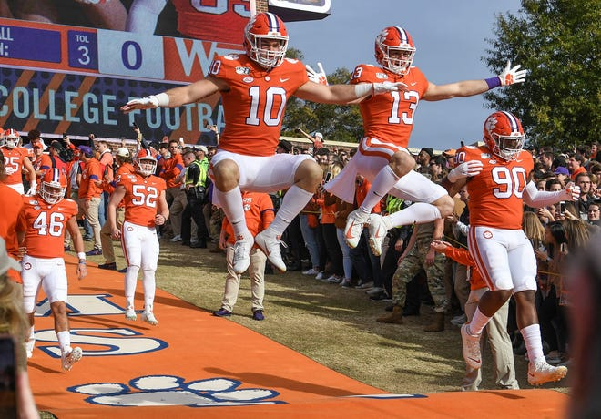 Clemson linebacker Baylon Spector, left, and wide receiver Brannon Spector leap as the Tigers run down the hill before a 2019 game. Both brothers are back this season.
