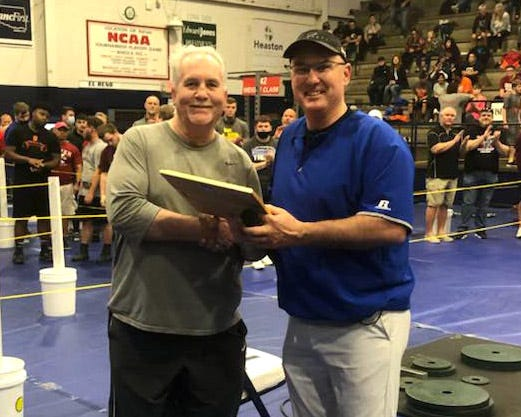 Kerry Roberts, left, receives a plaque after being inducted into the OFBCA Powerlifting Hall of Fame in March. Roberts graduated from Plainview High School in 1975.