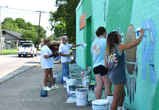 Volunteers paint a postcard-inspired mural on a wall along G Street Northwest near West Broadway Street Thursday, Aug. 29, 2021.