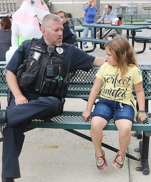 Ashland Police Officer Adam Brock talks with Hope Wells of Ashland during Thursday's Cones With A Cop at EVA's Treats.