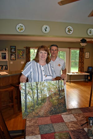 """Patti and Kevin Kimle pose at their Ames home with Patti's painting, which is the artwork for the cover of the book they co-wrote, """"The Only Free Road: an Underground Railroad Saga Unveiled."""""""