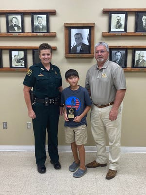 Bryce Fisher was presented a plaque and $200 for winning the D.A.R.E Essay Contest. He is pictured here with Deputy Malissa Sweeney and VPSO Chief Calvin Turner.