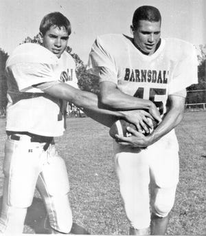 Barnsdall High quarterback Will McCauley, left, practices giving a handoff to running back Heath Dahl during a 1996 photo.