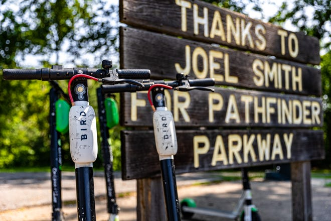 Bird and Lime scooters stationed along the entrance to the Bartlesville Pathfinder Parkway.
