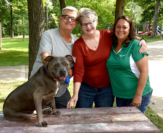 Stacy Stafford, right, president of People Helping Paws Dog Rescue, poses for a photo with David Gregg and Jill McDowell, who were foster parents and recently adopted Grace, 9, an American pit bull terrier.