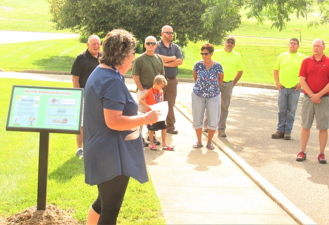 """Michele Skolmutch, director of Children's Services at the Holmes County District Public Library, addresses a gathering of village officials and library patrons Friday at the opening ceremony of the story walk called 'Walk With Me: A Community Adventure in Literacy"""" at Deer Run Park."""