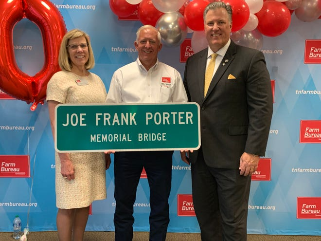 From left, TN Farm Bureau Executive Vice President Rhedona Rose, President Jeff Aiken and State Rep. Scott Cepicky hold new signage for the Joe Frank Porter Bridge, which will replace the existing signs off Williamsport Pike first erected in 1951 in tribute to the organization's founder and first president.