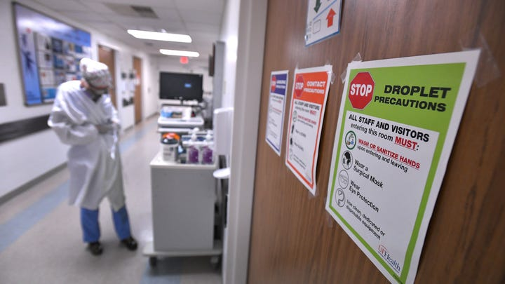 Signs on all the patient doors remind staff and visitors of precautions to prevent the spread of the Coronavirus in the COVID-19 ward at UF Health's downtown Jacksonville campus Friday, July 30, 2021. The second surge of COVID-19 infections in Jacksonville is stretching the capacity of area medical facilities to care for patients.