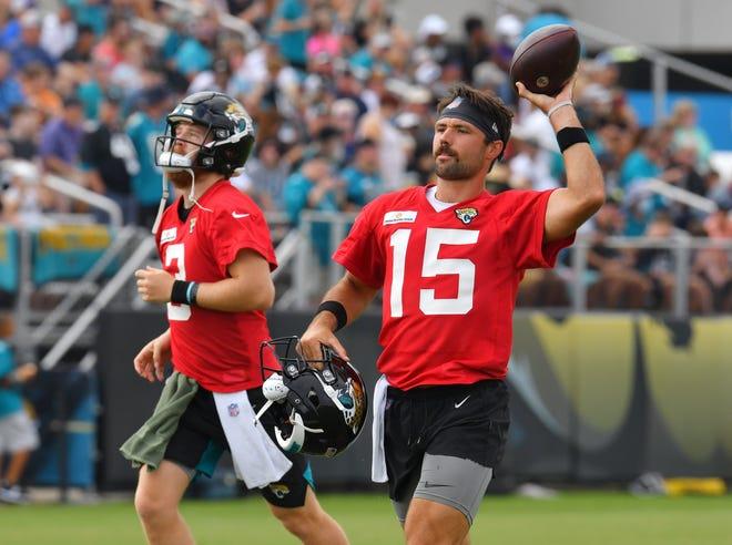 Jaguars quarterbacks Gardner Minshew (15) and C.J. Beathard (3) warm up before the start of Friday's training camp practice.