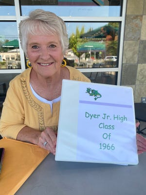 Susie Clendening, formerly Susie Stout, holds a binder she put together to keep track of her classmates from 1966.