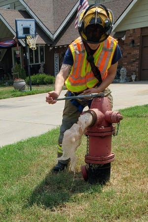 A firefighter in South Hutchinson opens a fire hydrant for an annual test. The city's fire department will be testing hydrants around town for the next two months.