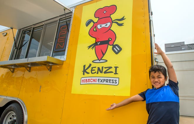 Kenzie Yasa, 8, proudly displays the artwork on the side of his dad Ikomang Kembaryasa's food truck, Kenzi Hibachi Express, at its permanent location at 3324 Court St. in Pekin. The new food truck is named after Kenzie with a slight spelling change.
