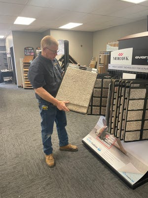 Eric Nystrom shows off carpet samples.