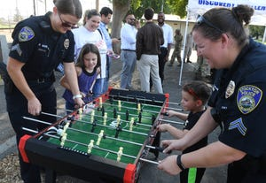 Stockton police Officer Melissa White joins Amanda Morris, left, as they take on Officer Katie Crawford and Tracin Morris during a National Night Out event at the McKinley Community Center in 2017.