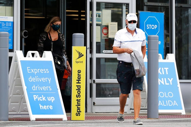 FILE - In this July 30, 2020 file photo, shoppers wear face masks as they leave a Walmart store in Vernon Hills, Ill. Walmart is reversing its mask policy, Friday, July 30, 2021, and will require vaccinated workers in its distribution centers and stores in areas to wear masks in areas with high infection rates of the virus. AP Photo/Nam Y. Huh, File