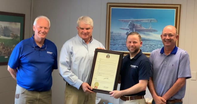 Missouri Senator Jason Bean (second from left) presents a copy of the Senate Resolution honoring the 100th anniversary of aerial application to (L-R) Dennie Stokes (Co-owner), Josh Rittenberry (Insurance Division) and Chris Cobb (Co-owner) of Mid-Continent Aircraft Corp.