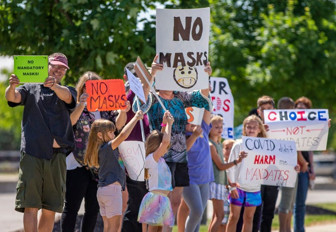 People hold up signs during an anti-mask demonstration by Strengthen Our Schools-PHM District on Friday, July 30, 2021, outside the Penn-Harris-Madison School Corporation in Mishawaka.