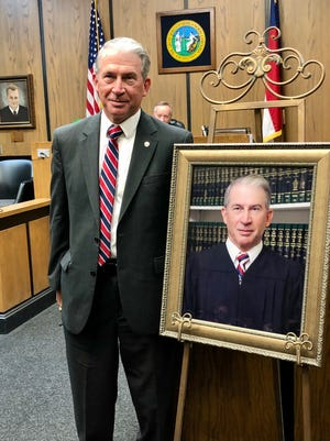 Judge Larry Wilson stands next to his portrait in the Cleveland County Courthouse. The portrait will remain on the walls of his courtroom.