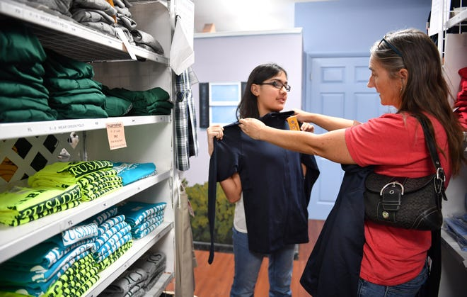 Constance Barbier, 13, an eighth grader at Incarnation Catholic School, gets help picking out a jacket from family friend Alison Vesco at Children's World on Thursday.