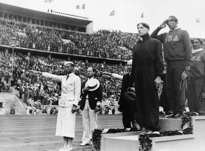 In this Aug. 3, 1936, photo, gold medalist Jessie Owens, second from right, salutes during the playing of the national anthem during the medal ceremony of the 100-meter final in Berlin. Silver medalist Tinus Osendarp, third from right, of Holland, and bronze medalist Ralph Metcalf, right, listen, along with a matron who holds a Nazi salute. The 1936 Games in Berlin, awarded about two years before Adolf Hitler became dictator, went ahead under Nazism. Owens went on to win four gold medals, but he was only supposed to compete in three events, the 100 meters, 200 meters and long jump.