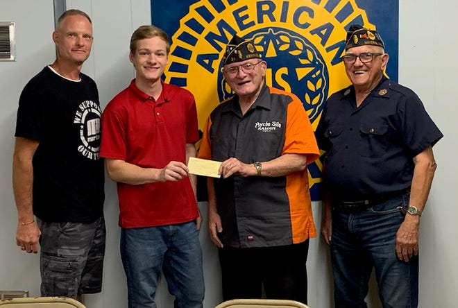 Kewanee American Legion Commander Ted Canellos, accompanied by post member Glenn Morey, awards the Roy C. Pettit Scholarship to Kewanee High School student Bryce Webster, who was joined by his father, Justin.