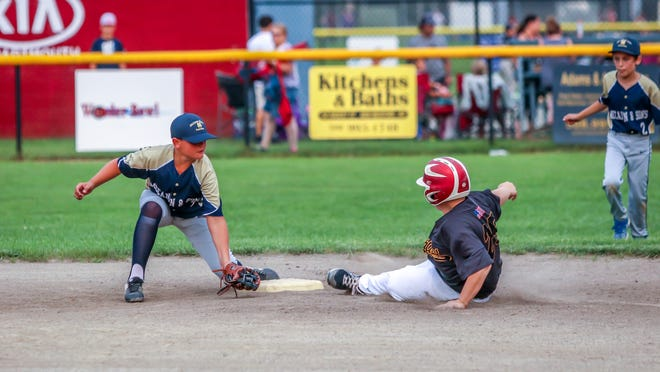 Drew Alfaiate of South Coast Towing is safe at second base, just sliding in before the tag of McCann & Son's shortstop Gabe Figueroa. South Coast would go on to win the much anticipated match up by a score of 8-0.