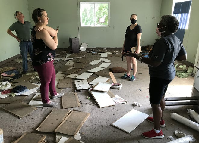 From left, PSU School of Construction Director Jim Otter, Katrina Ringler and Bethany Falvey of the Kansas Historical Society, and Donna Jackson Campbell Brice look at the interior of the long-disused Carver League building on Thursday.