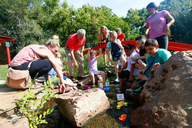 Children join Kansas Children's Discovery Center staff and representatives from Evergy on Friday morning at KCDC, 4400 S.W. 10th Ave., for the unveiling of a body of water to replace the pond that formerly existed there.