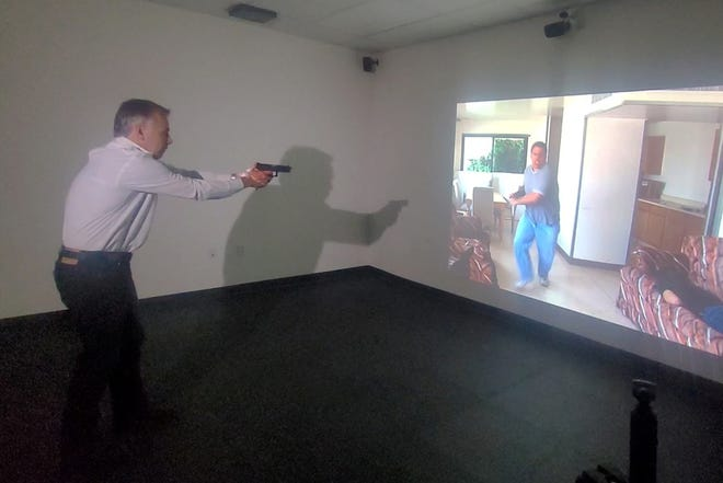 WHDH-TV reporter/anchor Steve Cooper shoots a suspect coming at him with a knife during a video use-of-force simulation presented by the U.S. Bureau of Alcohol, Tobacco, Firearms and Explosives Thursday at the Municipal Police Training Committee facility in Randolph.