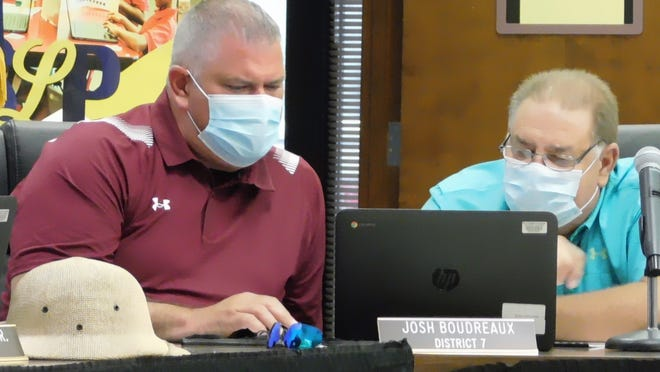 St. Landry Parish School Board members Josh Boudreaux (left) and Kyle Boss student an employee health care plan option that is on the Aug. 5 regular meeting agenda.