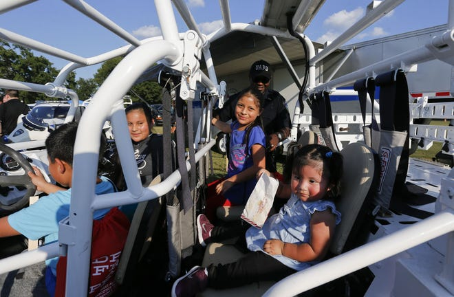 Officer Antonio Bostic from the University of Alabama Police Department shows a multipurpose vehicle to Jorge Manuel, Natalia Manuel, both in the front seat, Ramona Alice and Maria Francisco during the 2019 National Night Out. [Staff Photo/Gary Cosby Jr.]